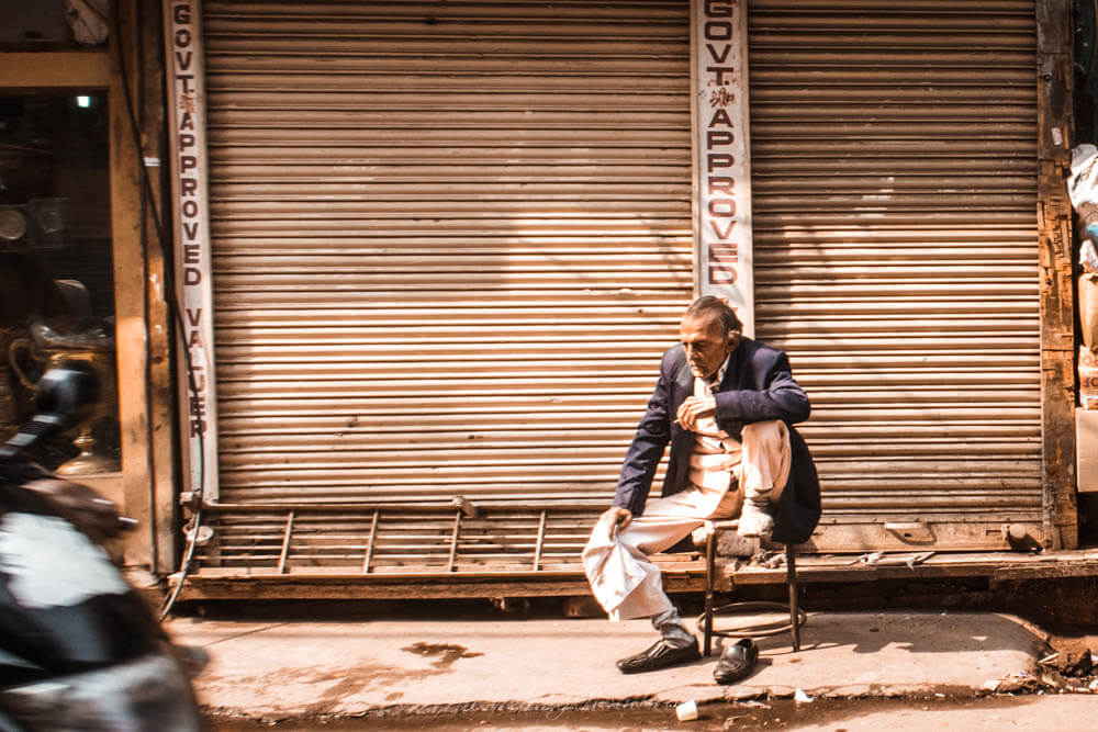 Chadni Chowk: A man sits alone amongst the busyness of Chadni Chowk
